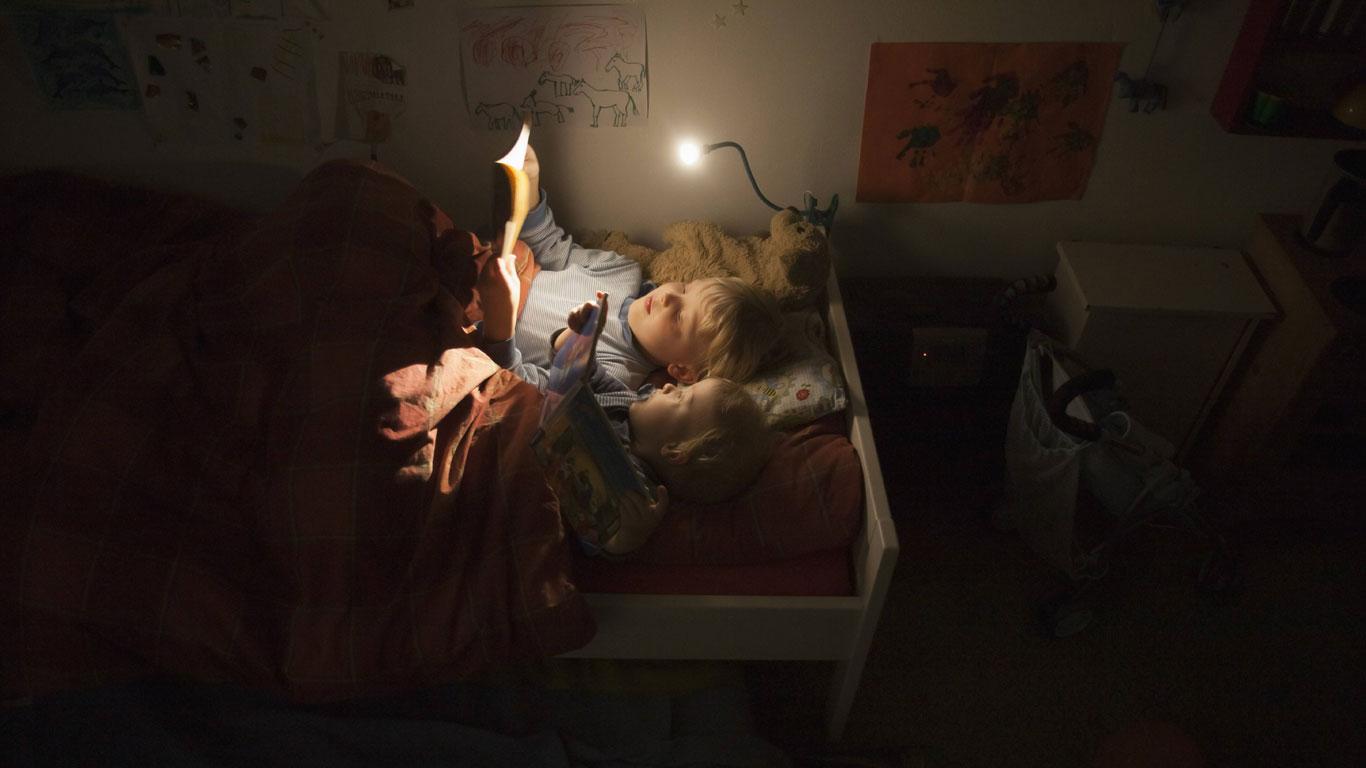 Kinder lesen im Dunkeln