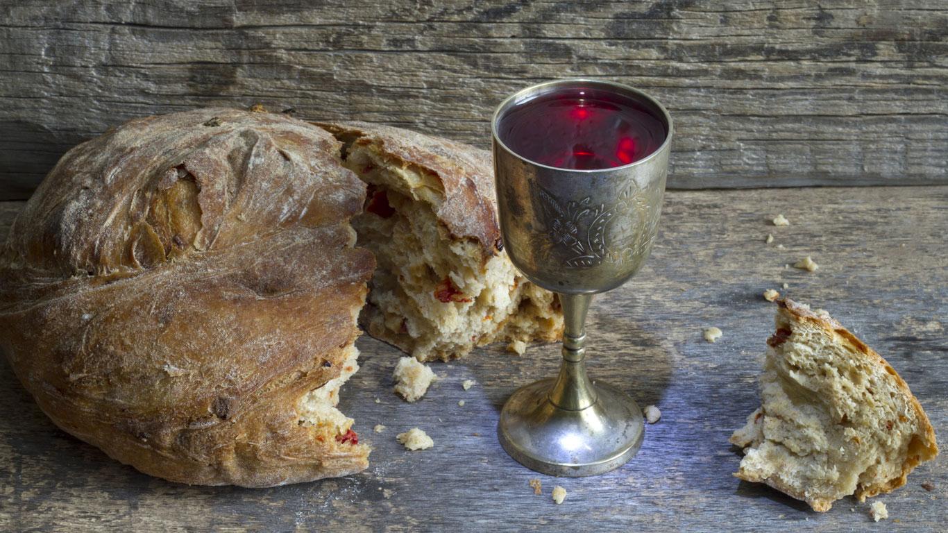 Silberner Kelch mit Wein neben einem Laib Brot