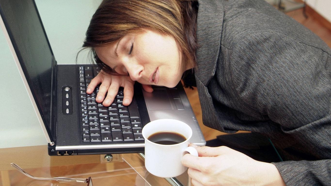 Frau schläft über Laptop ein