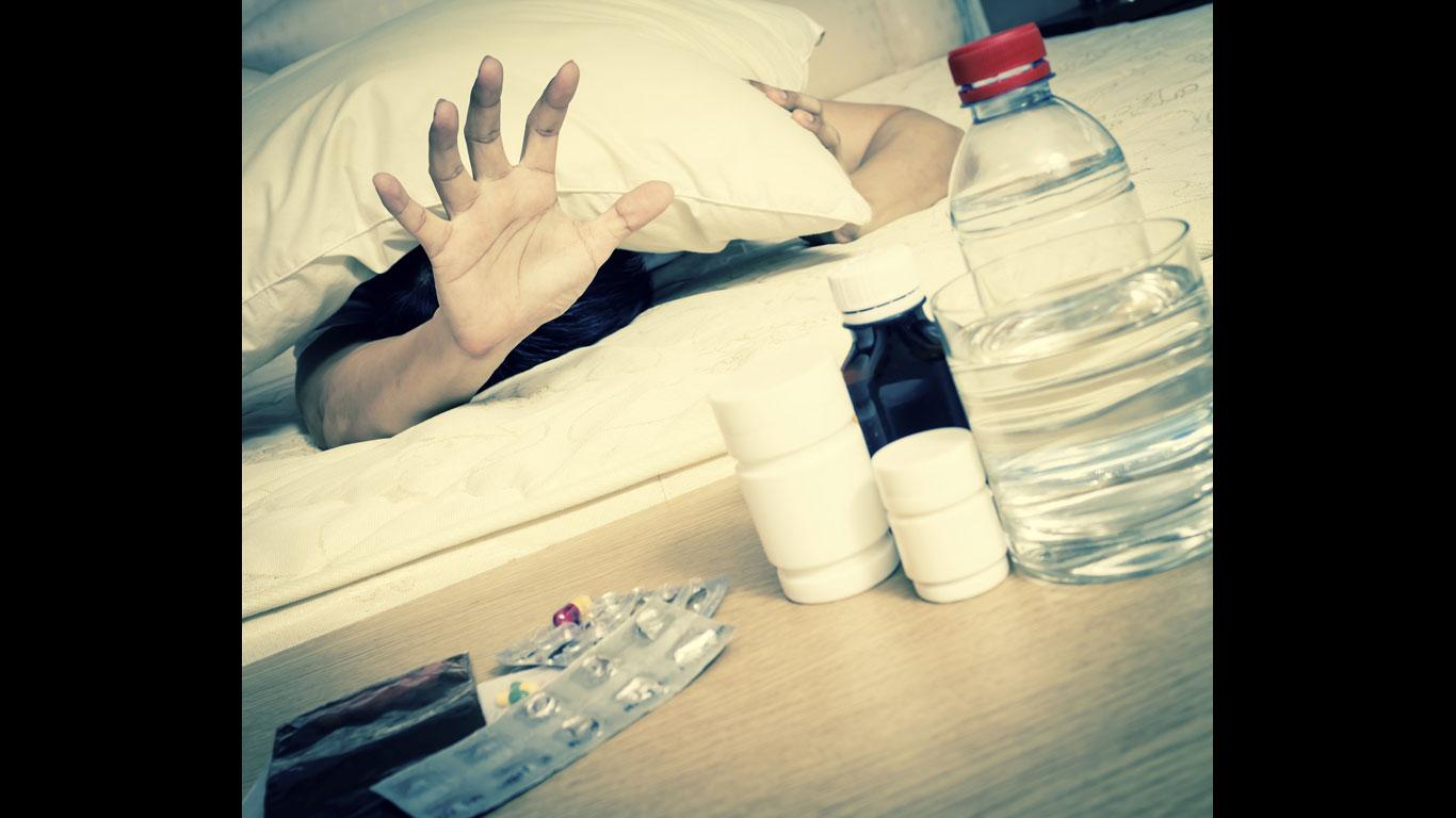 Hand greift nach Medikamenten